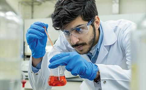 A scientist looking at red liquid in a vial