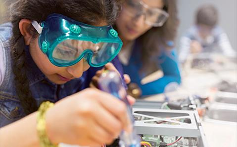 Science and tech education - a girl assembling electronics